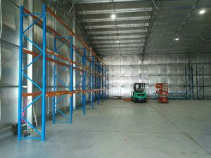 view inside warehouse shed with racking and forklifts